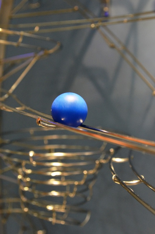 A Ball rests on a stainless steel track of Wave Rider Rolling Ball Sculpture